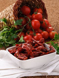 Dried tomatoes and fresh tomatoes stock images