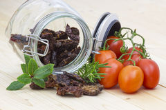 Dried tomatoes in a jar and fresh tomatoes Royalty Free Stock Photography