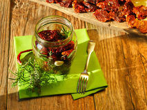 Dried tomatoes in jar. Sun dried tomatoes in jar; morning sun illuminates the situation, dried tomatoes on wooden blank in the background Stock Photos