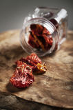 Dried tomatoes in a jar on a wooden board Royalty Free Stock Images