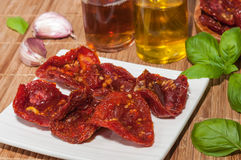 Dried tomatoes, olive oil, garlic and basil Royalty Free Stock Images