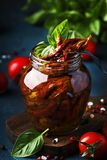 Dried tomatoes in olive oil with green basil and spices in glass jar on blue kitchen table, place for text royalty free stock photos