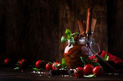 Dried tomatoes in olive oil with green basil and spices in glass jar on wooden kitchen table, rustic style, place for text royalty free stock photos