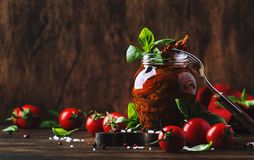 Dried tomatoes in olive oil with green basil and spices in glass jar on wooden kitchen table, rustic style, place for text royalty free stock image