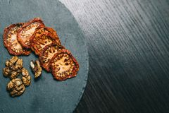 Dried tomatoes walnuts on a dark backgrounds royalty free stock photo