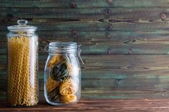 Dried traditional Italian pasta in storage jars. With long spiral fusilli bucati lunghi and mixed egg and green fettuccine on a rustic wood background with copy stock photo