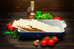 Dried uncooked lasagna pasta sheets and ingridients. On wooden background Stock Photo