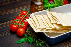 Dried uncooked lasagna pasta sheets and ingridients. On wooden background Stock Image