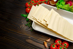 Dried uncooked lasagna pasta sheets and ingridients. On wooden background Stock Photography