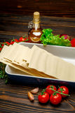 Dried uncooked lasagna pasta sheets and ingridients. On wooden background Royalty Free Stock Photo