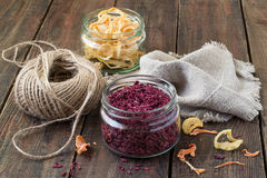 Dried vegetables, twine and linen cloth. Dried vegetables in jars (beets, onions), twine, linen cloth on a wooden background Stock Image