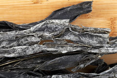 Dried Wakame Seaweed. Strips of dried wakame seaweed on a cutting board Royalty Free Stock Photos