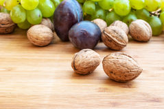 Dried walnuts on wooden background and grapes and plums in the back Royalty Free Stock Photos