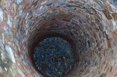 Dried well filled with plastic bottles; pollution