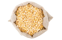 Dried yellow peas in sackcloth bag on white Stock Image