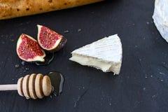 Driehoekig smakelijk stuk van camembertkaas, stukken van fig. in honing en een houten lepel voor honing en baguette op grafietb Stock Fotografie