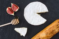 Driehoekig smakelijk stuk van camembertkaas, stukken van fig. in honing en een houten lepel voor honing en baguette op grafietb Stock Foto