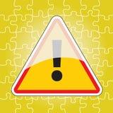 Driehoekig waarschuwingssein op raadsel Stock Foto