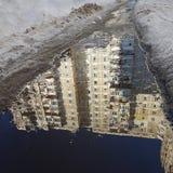 Driehoekige spiegelbezinning van een wit hoog huis in een de lentevulklei, langs de banken van vulklei smeltende sneeuw Stock Foto's
