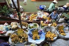 Driepersoons verkopend vruchten en voedsel bij het drijven van Damonen Saduak markt Stock Foto's