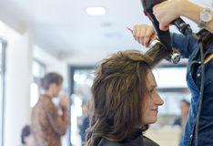 Dries hair in salon. Woman dries hair in hairdressing salon royalty free stock photography