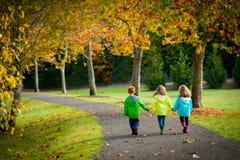 Drietalkinderen die op een treelined weg lopen Stock Fotografie