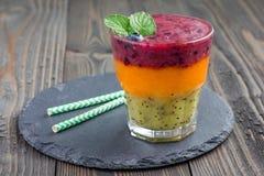 Drievoudige smoothie in glas: kiwi-munt, mandarin-abrikoos en aardbei-bosbes, exemplaarruimte Stock Fotografie