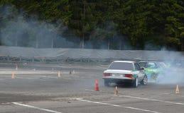 Racing: Sports cars Drifting. 2 cars performing simultaneous drifting royalty free stock photo