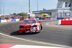 Red cars drift in front of the audience. stock image