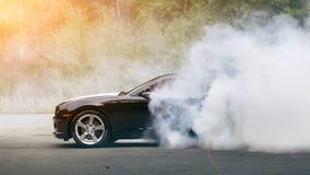 Drift - muscle car makes smoke. Drift - black muscle car makes lot of smoke stock photos