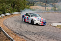 Drift racing car. A drift racing car BMW in action with smoking tires in hairpin bend at rally Predappio legend 2012, historical italian uphill race, on Juli 21 royalty free stock photography
