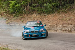 Drift racing car. A drift racing car BMW in action with smoking tires in hairpin bend at rally Predappio legend 2012, historical italian uphill race, on July 21 stock photo