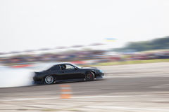 Drift racing. A drift racing car in action with smoking tires Stock Photography