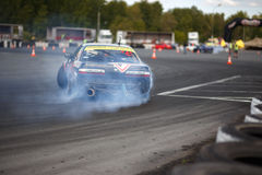 Drift racing car. Tyumen, Russia - May 31, 2014: A drift racing car in action with smoking tires in hairpin bend at Russian Drift Series Ural 2014 Royalty Free Stock Photo