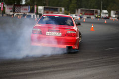 Drift racing car. Tyumen, Russia - May 31, 2014: A drift racing car in action with smoking tires in hairpin bend at Russian Drift Series Ural 2014 Royalty Free Stock Image