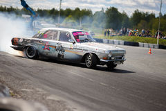 Drift racing car. Tyumen, Russia - May 31, 2014: A drift racing car in action with smoking tires in hairpin bend at Russian Drift Series Ural 2014 Royalty Free Stock Photos