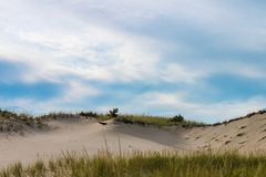 Drifted sand dunes with grass on the ridge-horizon under a blue sky stock photo