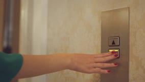 Driftig knapp för kvinnlig hand för att kalla hissen i lägenhetkorridor arkivfilmer