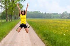 Driftig lättrörlig ung kvinna som hoppar för glädje Arkivbilder