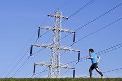 Driftig löpare på diket under elektricitetspylonen Royaltyfri Fotografi