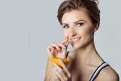 Driftig lycklig dricka orange fruktsaft för härlig ung idrotts- flicka, sund livsstil Royaltyfri Bild