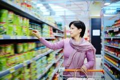 Driftig shoppingvagn för kvinna som väljer på gods i supermarket arkivfoto