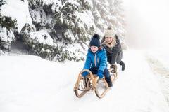 Driftig son för moder på pulkan Dimmig vit vinternatur royaltyfri bild