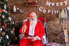 Driftiga Santa Claus lyfter upp tummen och att sitta på fåtöljen i fe arkivfoto