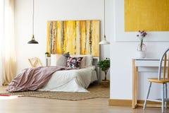 Driftigt sovrum med gult konstverk arkivfoto