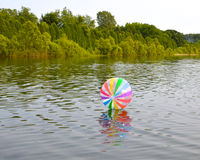Drifting Beach Ball. A brightly colored beach ball drifts on the surface of a placid lake Stock Image