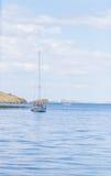 Drifting boat on lake Baikal in Siberia. White clouds over freshwater lake Baikal Stock Image