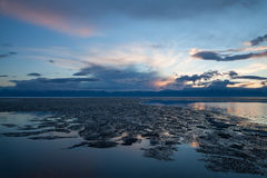 Drifting ice formations on water surface on sunset Stock Images