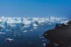 Drifting ice in the sea near the sandy coast. Ice in the sea near the beach royalty free stock photo