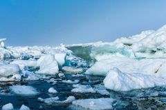 Drifting ice in the sea near the sandy coast. Ice in the sea near the beach stock images